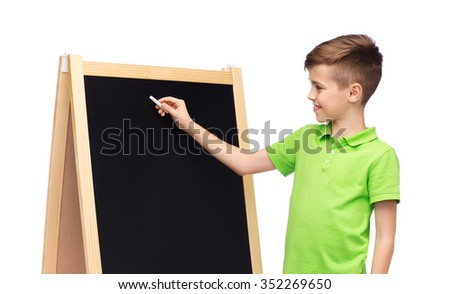 childhood, education, school, advertisement and people concept - happy smiling boy in green polo t-shirt with chalk and blank school blackboard - stock photo