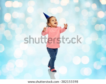 childhood, fashion, birthday, holidays and people concept - happy smiling african american little baby girl with birthday party hat playing and catching something over blue holidays lights background - stock photo