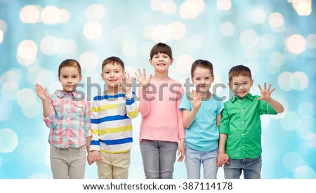 childhood, fashion, friendship and people concept - group of happy smiling little children holding hands over blue holidays lights background - stock photo