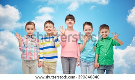 childhood, fashion, friendship and people concept - group of happy smiling little children holding hands over blue sky and clouds background - stock photo