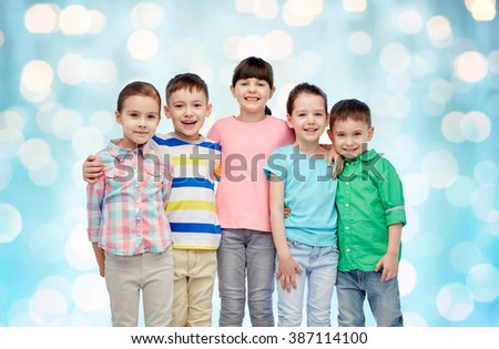 childhood, fashion, friendship and people concept - group of happy smiling little children hugging over blue holidays lights background - stock photo