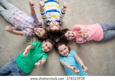 childhood, fashion, friendship and people concept - group of happy smiling little children lying on floor and showing thumbs up - stock photo