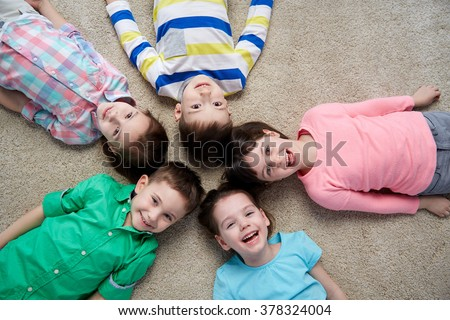 childhood, fashion, friendship and people concept - group of happy smiling little children lying on floor - stock photo