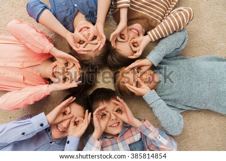 childhood, fashion, friendship and people concept - happy children lying in circle on floor, making faces and having fun - stock photo