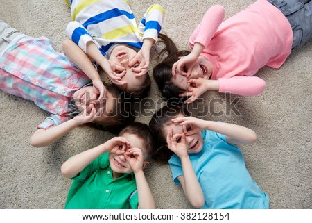 childhood, fashion, friendship and people concept - happy children making faces and having fun lying on floor in circle - stock photo