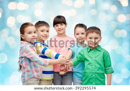 childhood, fashion, friendship and people concept - happy little children with hands on top over blue holidays lights background - stock photo