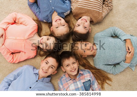 childhood, fashion, friendship and people concept - happy smiling children lying on floor in circle - stock photo