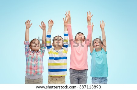childhood, fashion, gesture and people concept - happy smiling children raising fists and celebrating victory over blue background - stock photo