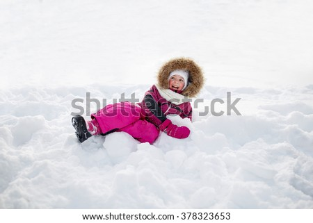 childhood, fashion, season and people concept - face of happy little kid or girl in winter clothes on snow