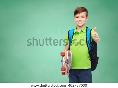 childhood, gesture, education and people concept - happy smiling student boy with backpack and skateboard showing thumbs up over green school chalk board background - stock photo