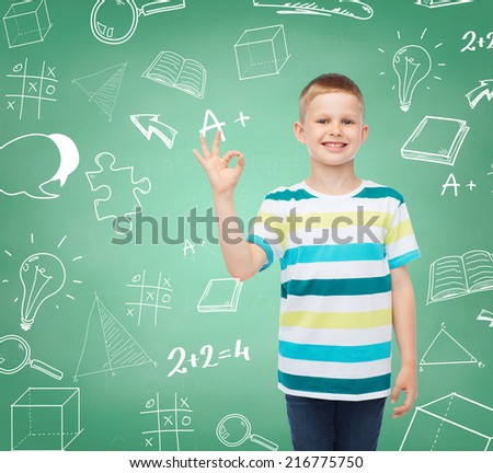 childhood, gesture, education and people concept - smiling little boy in casual clothes making OK gesture over green board with doodles background - stock photo