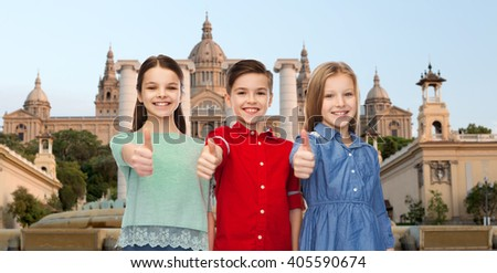 childhood, gesture, travel, tourism and people concept - happy smiling boy and girls showing thumbs up over national museum of barcelona background - stock photo