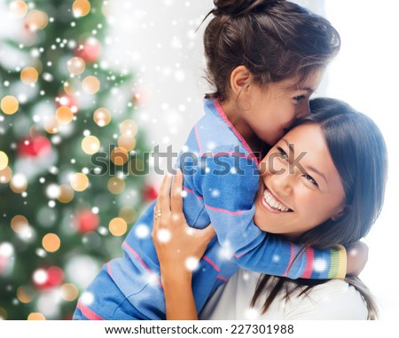 childhood, happiness, christmas, family and people concept - smiling little girl and mother hugging indoors over living room with tree - stock photo