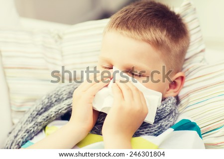 childhood, healthcare and medicine concept - ill boy with flu blowing nose at home - stock photo
