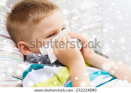 childhood, healthcare and people concept - ill boy with flu blowing nose into tissue at home - stock photo