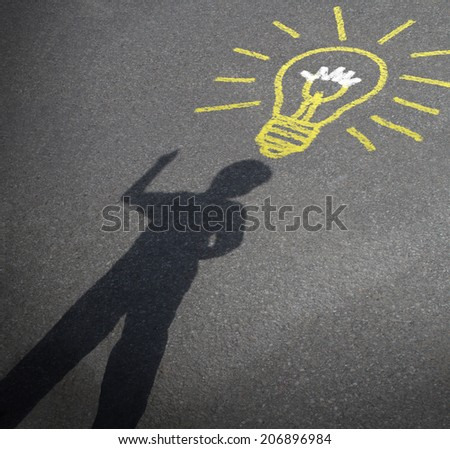Childhood imagination and child creativity concept as the shadow of an inspired boy with a lightbulb chalk drawing on asphalt as a symbol of inspiration and creative learning or back to school ideas.