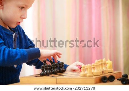 Childhood. Intelligent smart clever boy child kid preschooler playing chess. Leisure. At home. - stock photo