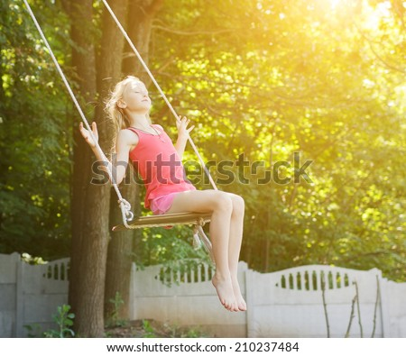 Childhood.Kid on swing.Looking fresh and happy - stock photo