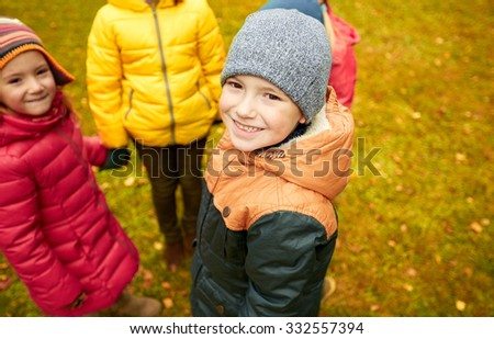 childhood, leisure, friendship and people concept - group of happy children holding hands and playing in autumn park - stock photo