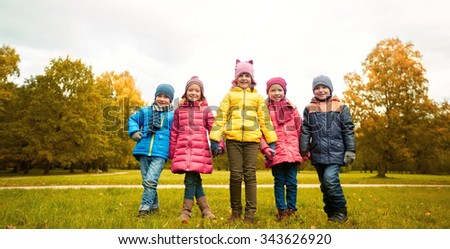 childhood, leisure, friendship and people concept - group of happy children holding hands in autumn park - stock photo