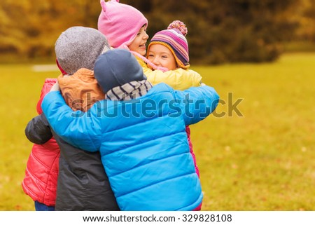 childhood, leisure, friendship and people concept - group of happy kids hugging in autumn park - stock photo