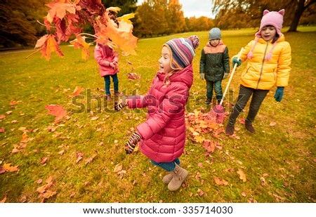 childhood, leisure, friendship and people concept - group of happy kids playing with and racking autumn maple leaves and having fun in park - stock photo