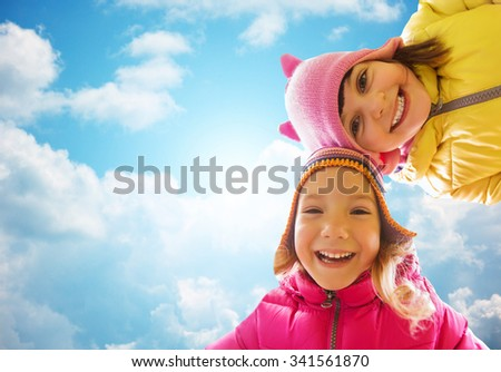 childhood, leisure, friendship and people concept - happy girls faces outdoors over blue sky and clouds background - stock photo