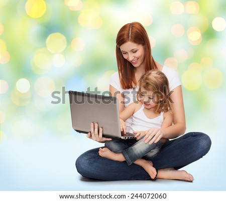 childhood, parenting and technology concept - happy mother with adorable little girl and laptop computer over green lights background - stock photo