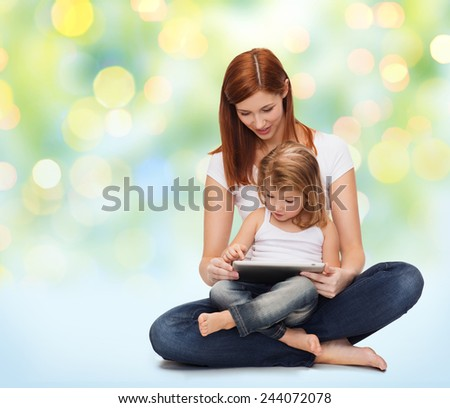 childhood, parenting and technology concept - happy mother with adorable little girl and tablet pc computer over green lights background - stock photo