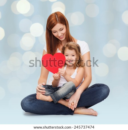 childhood, parenting, people and love concept - happy mother with adorable little girl holding red heart over holidays lights background - stock photo