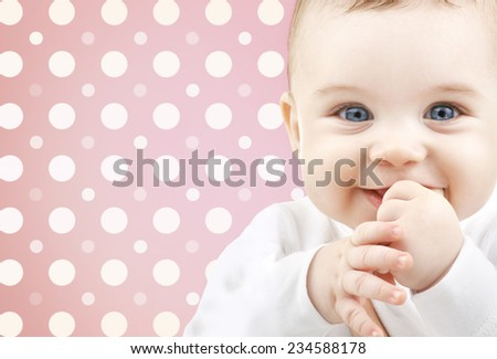 childhood, people and happiness concept - smiling baby girl face over pink and white polka dots pattern background - stock photo