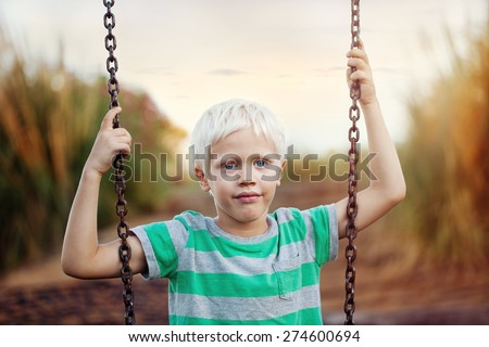 Childhood. Portrait of a positive boy (6 years) on a swing on a summer day .Outdoor, close up. - stock photo