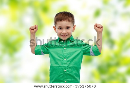 childhood, power, gesture and people concept - happy smiling little boy with raised hands showing his power over green natural background - stock photo