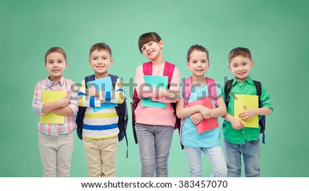 childhood, preschool education, learning and people concept - group of happy smiling little children with school bags and notebooks over green chalk board background - stock photo
