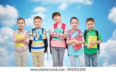 childhood, preschool education, learning and people concept - group of happy smiling little children with school bags and notebooks over blue sky and clouds background - stock photo