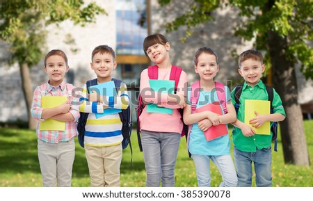 childhood, preschool education, learning and people concept - group of happy smiling little children with school bags and notebooks over summer campus background - stock photo