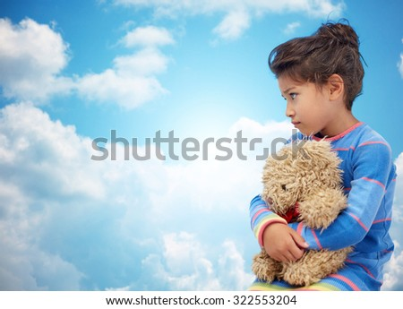 childhood, sadness, loneliness and people concept - sad little girl with teddy bear toy over blue sky and clouds background - stock photo