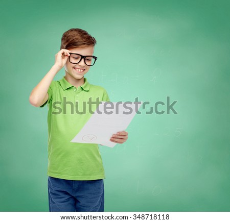 childhood, school, education and people concept - happy smiling boy in eyeglasses holding paper with test result over green school chalk board background - stock photo