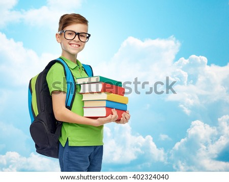 childhood, school, education and people concept - happy smiling student boy in eyeglasses with school bag and books over blue sky and clouds background - stock photo
