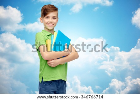 childhood, school, education and people concept - happy smiling student boy with folders and notebooks over blue sky and clouds background - stock photo