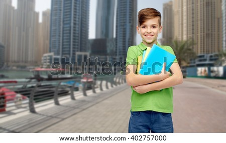 childhood, school, education and people concept - happy smiling student boy with folders and notebooks over dubai city street background - stock photo