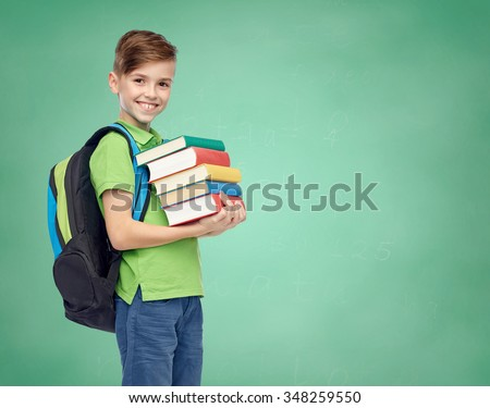 childhood, school, education and people concept - happy smiling student boy with school bag and books over green school chalk board background - stock photo