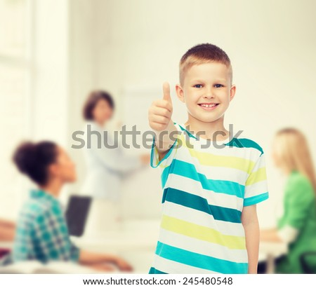 childhood, school, education and people concept - smiling little boy showing thumbs up over group of students in classroom - stock photo