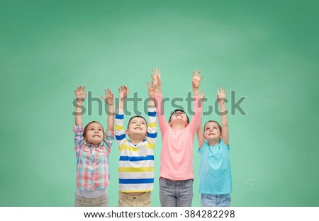 childhood, school, education, gesture and people concept - happy smiling children raising hands and celebrating victory over green school chalk board background - stock photo