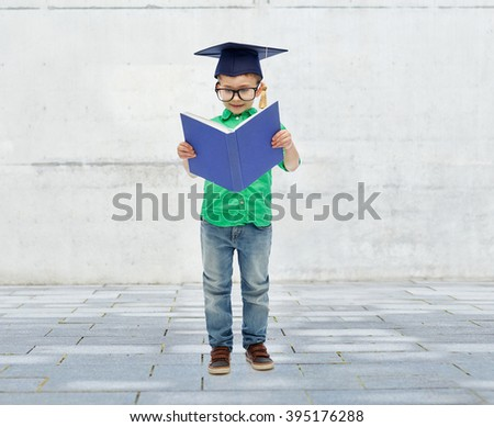 childhood, school, education, knowledge and people concept - happy boy in bachelor hat or mortarboard and eyeglasses over urban city street background - stock photo