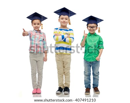 childhood, school, education, knowledge and people concept - happy children in bachelor hats or mortarboards and eyeglasses - stock photo