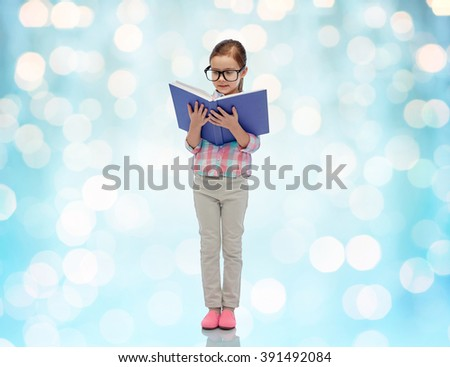childhood, school, education, vision and people concept - happy little girl in eyeglasses reading book over blue holidays lights background - stock photo