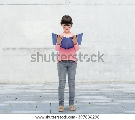 childhood, school, education, vision and people concept - happy little girl in eyeglasses reading book over urban city street background - stock photo