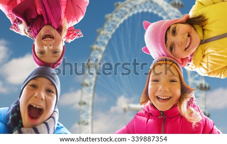 childhood, tourism, travel, vacation and people concept - happy little children faces outdoors over london ferry wheel background - stock photo