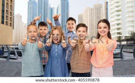 childhood, travel, tourism, gesture and people concept - happy smiling boy and girls showing thumbs up over dubai city street background - stock photo